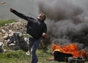 palestinian youth throws stone at israelis