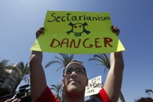 Lebanese secular activist, holds up a banner during a march calling for secularism and the abolishment of sectarianism, in Beirut, Lebanon, Sunday April 25, 2010.