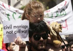 A Lebanese activist carries a sign demanding a secular system  ( Civil  Marriage is not a Civil  war) during a demonstration in front of parliament in Beirut April 25, 2010.