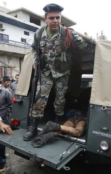A Lebanese soldier stands in an army truck next to the body of Egyptian Mohammed Mosallem that was stabbed to death in Ketermaya village