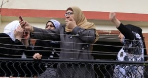 Residents  react as they take pictures of the hanging body of Egyptian Mohammed Msallem after he was stabbed to death in Ketermaya village in Mt Lebanon