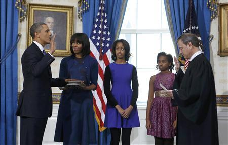 U.S. President Obama takes the oath of office from U.S. Supreme Court Chief Roberts as first lady Michelle holds the bible and daughters Malia and Sasha look on in the Blue Room of the White House in Washington