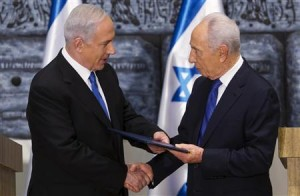 Israeli PM Netanyahu receives a folder from President Peres in a brief ceremony at the president's residence in Jerusalem