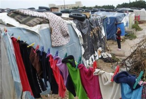 Syrian girl looks on as clothes are left hanging on a line at a refugee camp in the city of Tyre, in southern Lebanon
