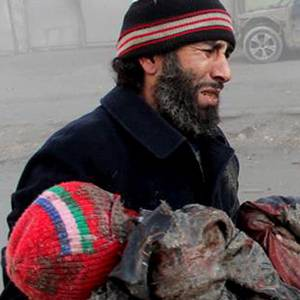 A syrian man cries while holding the body of a child who was killed in an a  Syrian government airstrike in Aleppo