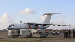 Workers load humanitarian aid from United Nations onto a plane for Syrian families, in Arbil airport