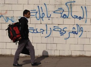 A student of Al-Azhar University walks along a wall covered with graffiti near a bus damaged by a bomb blast around the Al-Azhar University campus in Cairo's Nasr City district