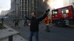 A security personnel shouts as smoke rises from the site of an explosion in Beirut's downtown area