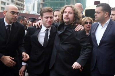 Omar, left, and Ronnie Shatah, the sons  of slain former Finance Minister Mohammad Shatah, embrace during their father 's funeral procession outside of the Mohammad al-Amin Mosque in Beirut, Sunday, Dec. 29, 2013.