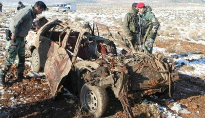 Members of the Lebanese army inspect the wreckage of the car .December 17, 2013.