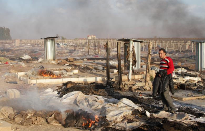 A man walks in a burnt makeshift Syrian refugee camp after it was attacked by residents of the neighboring eastern Lebanese village of Qsarnaba near Zahle in the Bekaa valley on December 2, 2013. (Photo: AFP / STR)
