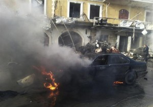 A man reacts near a burning car at the site of an explosion in the Shi'ite town of Hermel