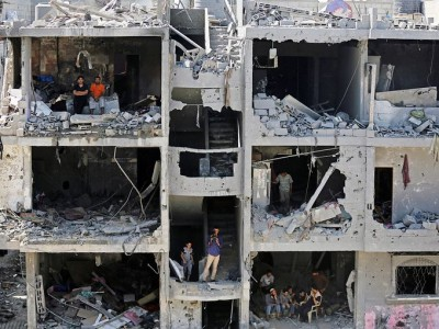Palestinians sit on rubble of houses destroyed after Israeli airstrikes in Rafah, southern Gaza Strip.  August 17, 2014 (Photo: Mohammed Saber, European Pressphoto Agency)