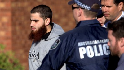 A man is led away by police as simultaneous raids are carried out across Melbourne.