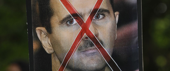 A protester holds up a poster of Syrian President Bashar al-Assad with cross mark over it during a protest rally against Assad's regime outside the Syrian embassy in Kuala Lumpur, Malaysia, Friday, June 8, 2012.    (AP Photo/Vincent Thian)