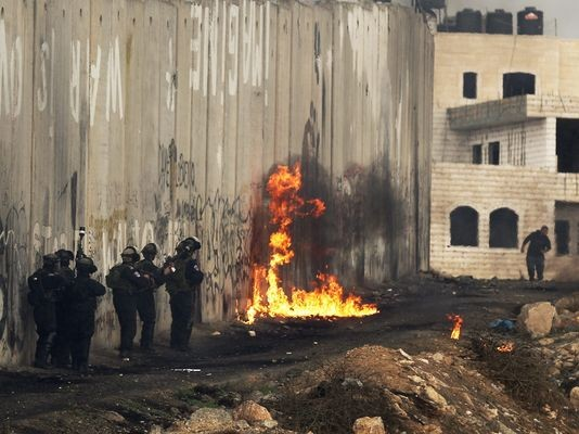 A Molotov cocktail explodes next to the separation barrier as as Israeli security forces take up positions during clashes with Palestinians at Kalandia checkpoint between the West Bank and Jerusalem on Oct. 31, 2014.