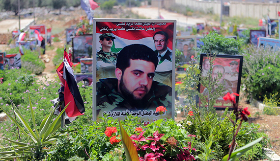 The portrait of a Syrian soldier who died during the Syrian conflict is seen at the Martyr's Cemetery in the city of Tartus, Syrian Alawites  are horrified by rising death toll.  May 18, 2014. (photo by AFP PHOTO/JOSEPH EID)