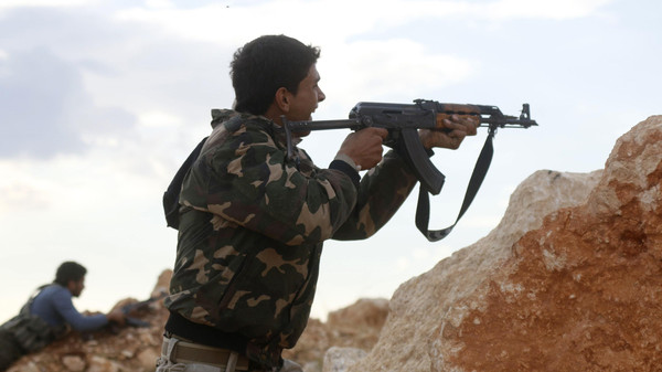 Free Syrian Army fighters shoot their weapons during clashes with forces loyal to Syria's President Bashar al-Assad around Handarat area October 16, 2014. REUTERS/Stringer