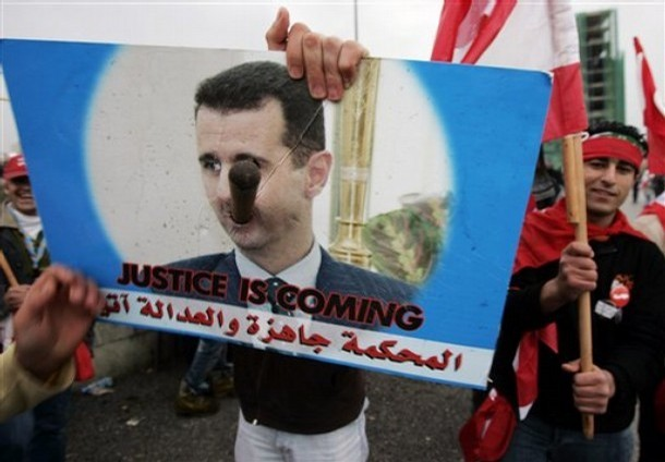A Lebanese anti-Syrian protester holds a poster against Syrian President Bashar Assad during the third anniversary of the assassination of former Lebanese Prime Minister Rafik Hariri in downtown of Beirut, Lebanon, Thursday, Feb. 14, 2008.