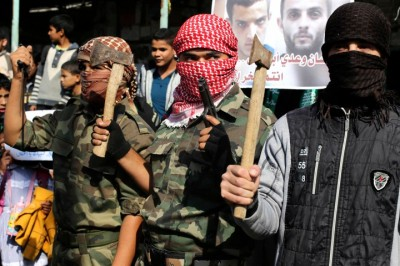 Masked Palestinians hold axes and a gun as they celebrate with others an attack on a Jerusalem synagogue, in Rafah in the southern Gaza Strip November 18, 2014.