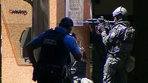 This image taken from a live video feed shows police in Sydney in a standoff outside a cafe where hostages are being held. (Seven/ABC)