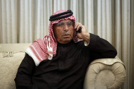 Safi al-Kasaesbeh, father of Jordanian pilot Muath, who was captured by Islamic State after his plane came down near Raqqa in Syria on Wednesday, speaks on a telephone as he follows the news of his son in the house of a relative in Amman December 25, 2014. CREDIT: REUTERS/MUHAMMAD HAMED