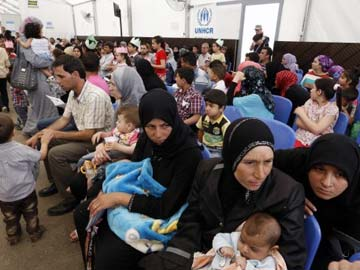 Syrian refugees gather in a room as they wait to be registered at a UNHCR (United Nations Refugee Agency) registration center, one of many across Lebanon, in the northern port city of Tripoli on May 29, 2014. The Lebanese have borne direct and indirect costs of nearly $20 billion as a result of the Syrian refugee crisis