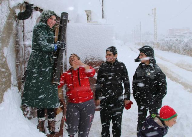 Syrian refugees stand amidst a snow storm at an unofficial camp on the road between Riyaq and Baalbek in Lebanon's eastern Bekaa Valley, near the border with Syria, on January 7, 2015