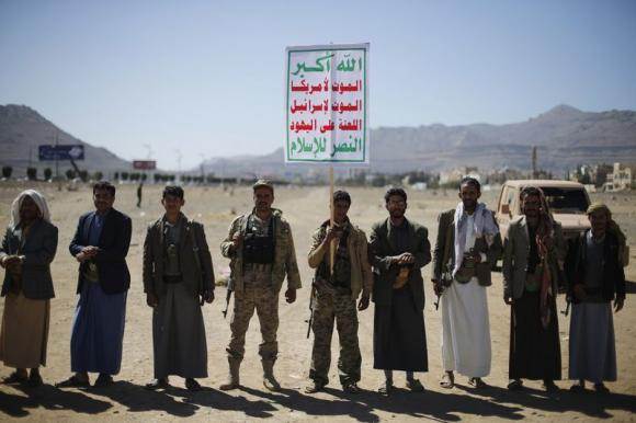 Followers of the Houthi movement attend a gathering to show support to the movement outside the Presidential Palace in Sanaa February 4, 2015. The banner reads: ''Allah is the greatest. Death to America. Death to Israel. A curse on the Jews. Victory to Islam''.