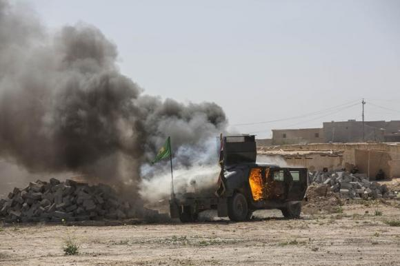 A military vehicle, belonging to the Irani-led  Shi'ite fighters known as Hashid Shaabi, burns after being hit by Islamic State militants, during clashes in northern Tikrit, March 11, 2015. CREDIT: REUTERS/STRINGER