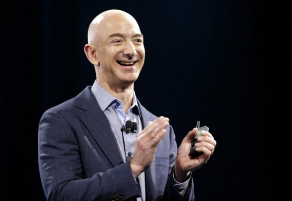 Amazon CEO Jeff Bezos holds a slide show controller and applauds at the start of the launch event for the new Amazon Fire Phone, Wednesday, June 18, 2014, in Seattle. (AP Photo/Ted S. Warren) ORG XMIT: WATW115