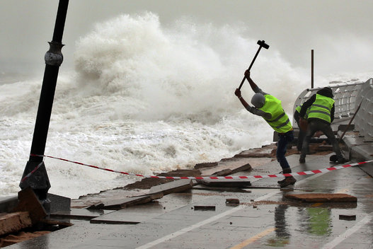 Municipal workers remove broken tiles near the fence of Beirut's seaside corniche which was damaged by strong and high waves in Lebanon, Feb. 11, 2015.