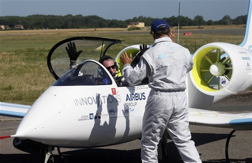 Pilot Didier Esteyne, left, raises his arms after crossing the Channel with his European planemaker Airbus E-Fan prototyp, at the Calais Airport, Friday, July 10, 2015. Airbus flew its electric plane across the English Channel for the first time Friday, hours after a French pilot made a similar voyage in his electric plane — journeys seen as a symbolically important step toward making electronic flight viable in the long term. (AP Photo/Michel Spingler)