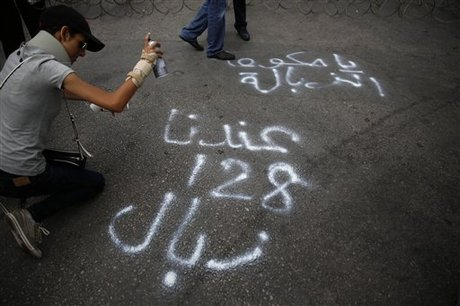 "A Lebanese protester spray paints graffiti against the Lebanese government, during a demonstration against the ongoing trash crisis, in front of the government house, in downtown Beirut, Lebanon, Tuesday, July 28, 2015. Protesters have closed the main roads in downtown Beirut over the country's trash crisis. The Arabic reads, ""We have 128 garbage collectors, Trash government."" (AP Photo/Hassan Ammar)"