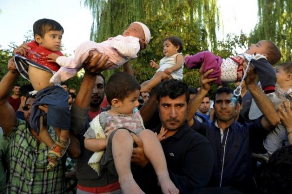 Migrants lift their children as they protest to be allowed to cross into Greece near the Turkish border in Edirne, September 20, 2015.  REUTERS/Alexandros Avramidis