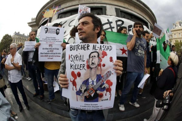 A protester holds a placard with a painting of Bashar al-Assad reading 'Butcher Al Assad, Syrial Killer - Dear Europe, It only needs to get one out, not to have to welcome millions.'