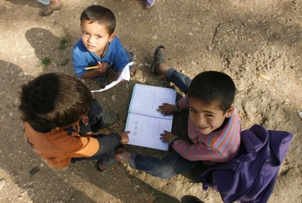 Boys play with a school book at a UNHCR's camp for Syrian refugees in south Lebanon on April 14, 2015. More than 12 million children in the Middle East are not being educated, despite advances in efforts to expand schooling, the UN children's agency UNICEF said. The figure does not include children forced from school by the conflicts in Syria and Iraq, who would bring the total not receiving an education to 15 million, the agency said in a new report.  AFP PHOTO / MAHMOUD ZAYYAT        (Photo credit should read MAHMOUD ZAYYAT/AFP/Getty Images)
