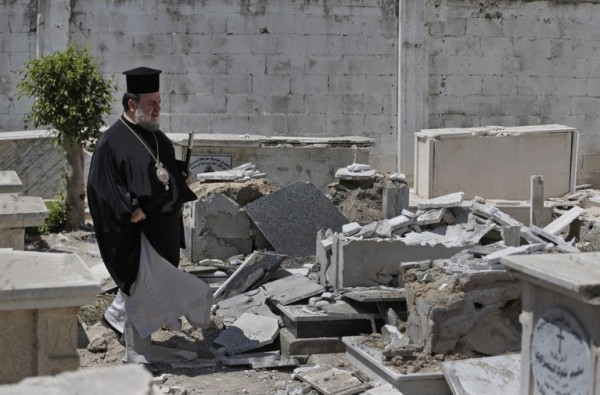 Greek Orthodox Archbishop of Gaza Alexios, walks past destroyed graves, hit by an Israeli strike, at the cemetery of the St. Porphyrios church in Gaza City, Sunday, Aug. 10, 2014. There are approximately 2,500 Christians among an overall Palestinian population of more than 1.7 million in Gaza. (AP Photo/Lefteris Pitarakis) ORG XMIT: XLP305
