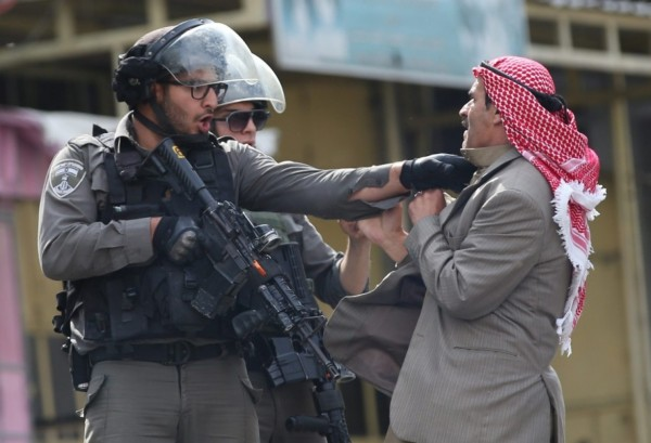 A Palestinian argues with Israeli policemen during clashes in the West Bank city of Hebron this month. (EPA/ABED AL HASHLAMOUN)