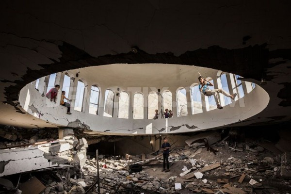 Children playing under the dome on the ground of the destroyed Ebad El Rahman mosque in Khuzaa village in the south of Gaza. May 2014