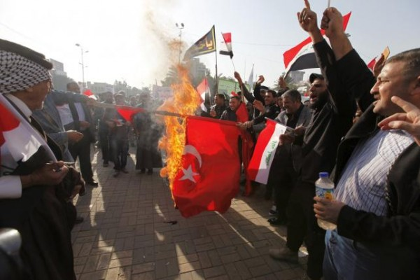 Protesters burn a Turkish national flag during a demonstration against the Turkish military presence in Iraq, at Tahrir Square in central Baghdad, Iraq, December 12, 2015. The rallies were organized and led by Shi'ite militia groups,  REUTERS/Ahmed Saad