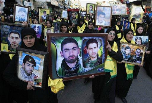 この2014年11月7日(金曜日)ファイルの写真では、レバノンのヒズボラの支持者はNabatiyehの南部市場の町で、Ashouraの13日目をマークするためにラリーの間に、シリアとイスラエルとの戦いで殺されたヒズボラの戦闘機の写真を運びます、レバノン。 南レバノンでしっかりと守ら施設で、17ほどの若い男性は、大統領バシャールアサド軍と一緒に戦うためにシリアにオフに出荷される前に、自動小銃や重機関銃を使用する方法について集中的な訓練を受けています。 トレーニングは今イスラエルの占領との戦いの18年の間にグループが負担するの死者数に近づいて、シリアの戦争でその人間の損失を補うために大規模なヒズボラ募集努力の一環です。(AP写真/モハメッドザータリ、ファイル)