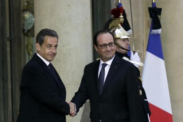 French President Francois Hollande (R) shakes hands with former French President Nicolas Sarkozy, head of the French conservative party UMP party, prior to a meeting at the Elysee Palace in Paris, January 8, 2015, the day after a shooting at the Paris offices of Charlie Hebdo.  REUTERS/Philippe Wojazer