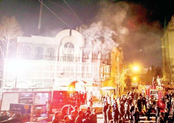 moke rises as Iranian protesters set fire to the Saudi embassy in Tehran on Jan 3. (AP)