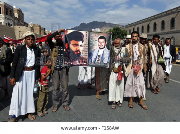 Houthi rebels hold a poster of Hezbollah chief Hassan Nasrallah  and Houthi chief Abdulmalik al-Houthi