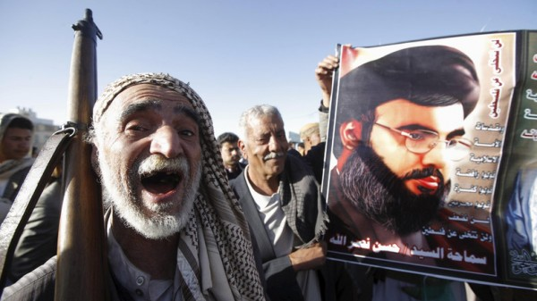 A Houthi militant shouts slogans as he stands next a poster of Lebanon's Hezbollah leader Sayyed Hassan Nasrallah during a rally against U.S. support to Saudi-led air strikes, in Yemen's capital Sanaa, February 19, 2016. REUTERS/Mohamed al-Sayaghi