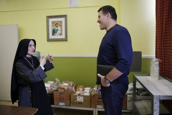 Sister Mary Valerie chats with Tony Robbins as she leads him on a tour at Fraternite Notre Dame Mary of Nazareth Soup Kitchen