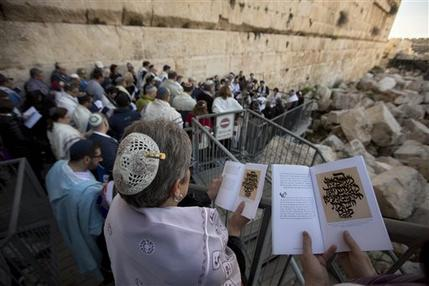 In this photo taken Thursday, Feb. 25, 2016, American and Israeli Reform rabbis pray in the Western Wall, the holiest site where Jews can pray in Jerusalem's old city. A recent gathering of American Reform rabbis in Jerusalem was meant to celebrate the small gains the liberal Jewish movement has made in Israel in recent years. But a series of comments by Israeli leaders denigrating the group marred the event, reflecting an awkward relationship that many fear is alienating the world's second-largest Jewish community from Israel. (AP Photo/Sebastian Scheiner)