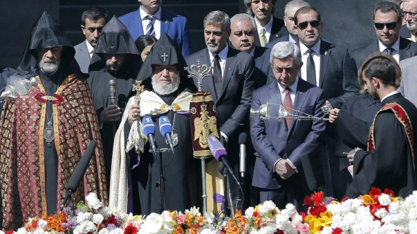 Armenian clergymen, US actor George Clooney, center, Armenian President Serzh Sargsyan, second right front, and guests attend a ceremony at a memorial to Armenians killed by the Ottoman Turks, in Yerevan, Armenia, on Sunday, April 24, 2016. (Vahan Stepanyan/ PAN Photo via AP)