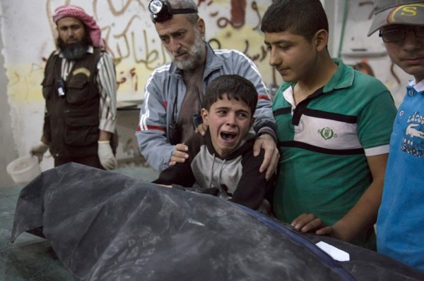 A Syrian boy is comforted as he cries next to the body of a relative who died in a reported airstrike on April 27, 2016, in the rebel-held neighborhood of al-Soukour in the northern city of Aleppo. A series of airstrikes and shelling by the Syrian government has left more than 60 people dead in less than 24 hours in the city of Aleppo in Syria on April 28 (Karam Al-Masri/AFP/Getty Images)